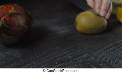 Chef Cuts Kiwi with Knife On Dark Wooden Table