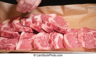 Chef cuts meat. Fresh raw meat on metal plate on dark table....