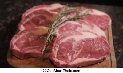 Chef cuts meat on wooden cut board. Fresh raw meat in...