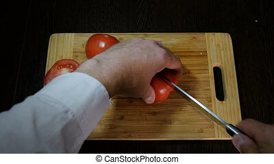 Chef cuts red tomatoes for salad