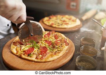 Chef cuts the pizza into slices