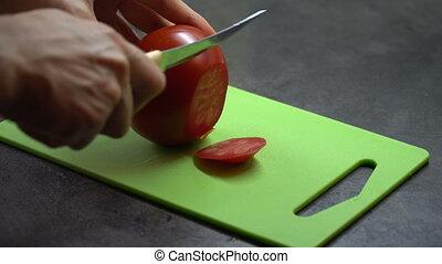 chef cuts the tomato on the board