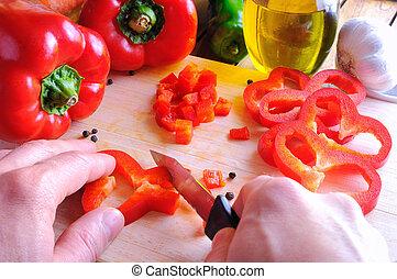 Chef cutting a red pepper on a cutting board