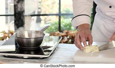 Chef cutting cheese.