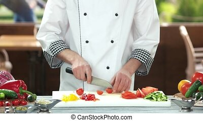 Chef cutting cherry tomato.