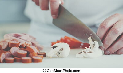 Chef cutting mushrooms for pizza in a restaurant
