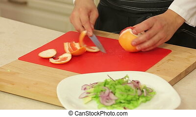Chef cutting orange fillet for salad