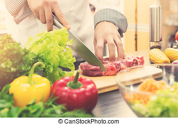 chef cutting raw meat on wooden board in kitchen