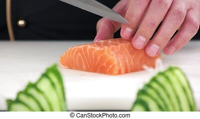 Chef cutting salmon close up. Sliced raw fish.