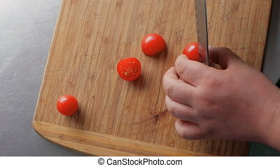 chef cutting tomatoes on a wooden board in the restaurant kitchen. cooking salad step by step