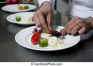 Chef decorating appetizer in a restaurant kitchen