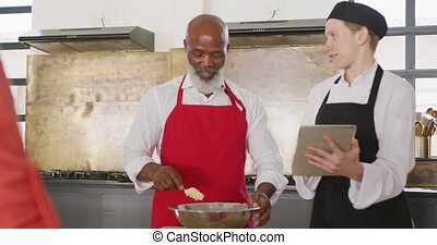 Chef explaining what to do - Front view of a senior African ...