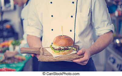 chef finishing burger - master chef putting toothpick on a ...