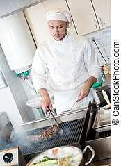 chef frying beef steak on grill - chef man in uniform frying...