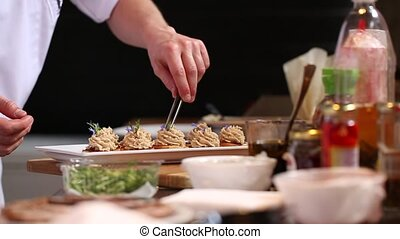 Chef garnishes pate with edible purple petals