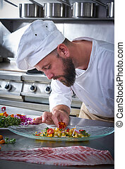 Chef garnishing flower in ceviche dish with hands at...