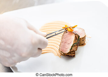 Chef garnishing meat dish