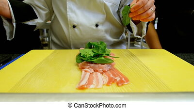 Chef garnishing meat with in kitchen 4k