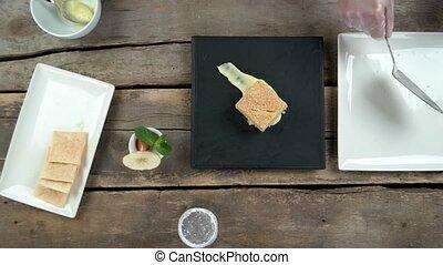 Chef garnishing napoleon cake. Dried apple, mint and...