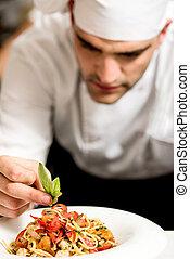 Chef garnishing pasta