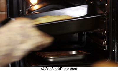 Chef gets baking bread from the oven