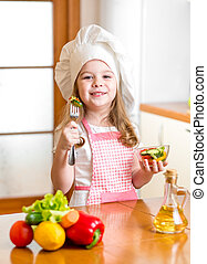 Chef girl preparing and tasting healthy food over white background