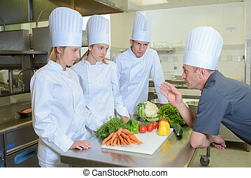 Chef giving instructions to trainee cooks