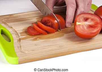 Chef Hand and Knife Slicing Tomato