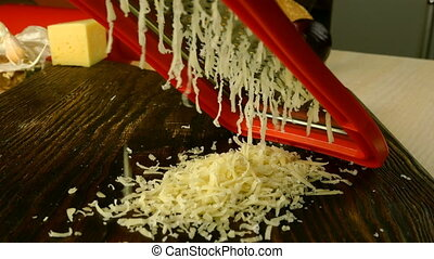 Chef hand are grating cheddar cheese for cooking pizza, pasta or another dish on dark cutting board with metal grater. Pile of grated cheese. Home cooking. Close-up.