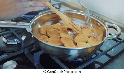 chef hand fry stir in a pan chicken nuggets tempura in to hot oil pan for deep fry cooking. chicken curry nuggets on a frying pan, kebab style. Frying the chicken nuggets lifestyle