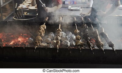 Chef hands cooking roasted meat barbecue with lots of smoke. Grilled shish kebab on metal skewer