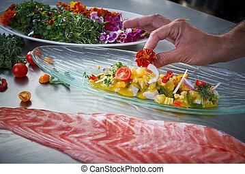 Chef hands garnishing flower in ceviche dish
