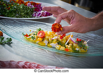 Chef hands garnishing flower in ceviche dish at stainless...