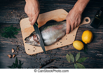 chef hands with a knife cutting fish on a wooden table in the kitchen. Fresh trout
