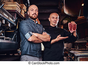 Chef holding a fresh steak and his assistant standing near in a restaurant kitchen.