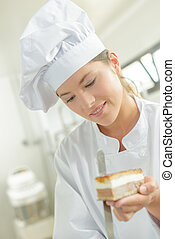chef holding a piece of cake