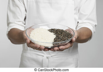 Chef holding bowl of white and wild rice (mid section)