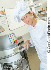 Chef holding handle of industrial machine