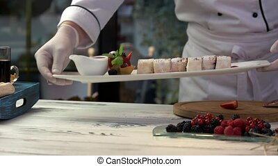 Chef holding plate with dessert.