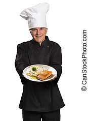Chef holding plate with roasted salmon.