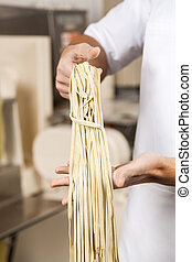 Chef Holding Spaghetti Pasta At Kitchen