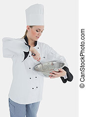 Chef holding wire whisk and mixing bowl - Young female chef...
