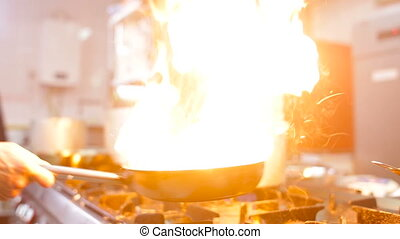 Chef in a kitchen cooking flambe style