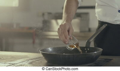 Chef in a kitchen making flambe.