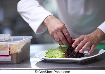 chef in hotel kitchen preparing and decorating food