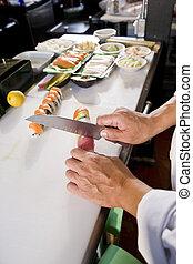 Chef in Japanese restaurant preparing sushi rolls
