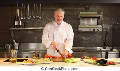 Chef in kitchen chopping vegetables.