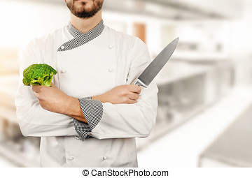 chef in restaurant kitchen with broccoli and knife in hands
