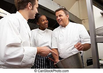 Chef Instructing Trainees In Restaurant Kitchen