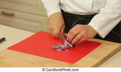 Chef is chopping red onion and boning date fruits